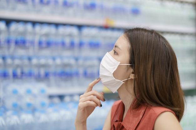 Covid-19 surto de propagação. mulher no pânico médico da máscara protetora que compra a água bebendo. medo de coronavírus.