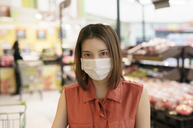 Covid-19 surto de propagação. mulher no pânico médico da máscara protetora que compra alimentos. medo de coronavírus.