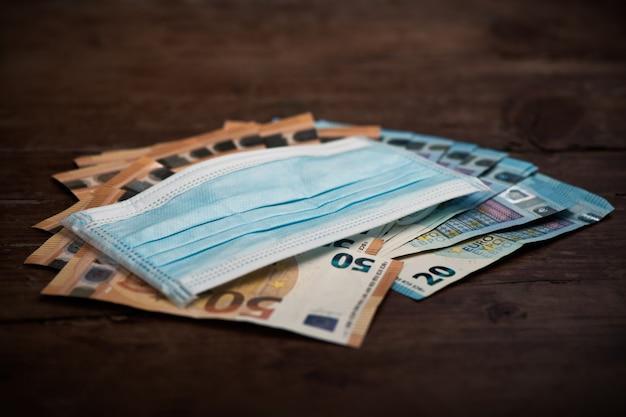 Covid com notas de euro e máscara facial. fechar-se