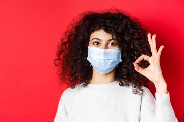 Covid e o conceito de saúde. mulher jovem confiante na máscara médica, mostrando o gesto de aprovação, garantia de qualidade, de pé na parede vermelha.