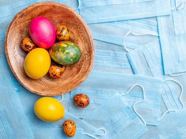 Covid flat coloca ovos de páscoa coloridos em um fundo de máscaras médicas azuis