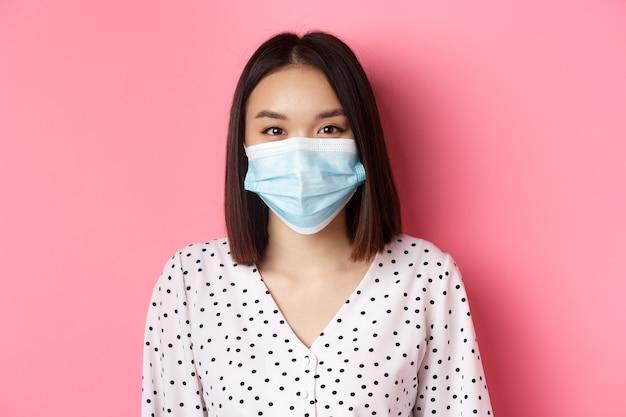 Covid pandemia e closeup de conceito de estilo de vida da bela mulher asiática em máscara facial sorrindo com os olhos ...