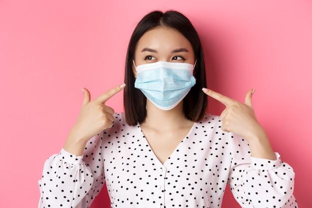 Covid pandemia e conceito de estilo de vida kawaii menina asiática apontando os dedos para a máscara facial usando pre ...