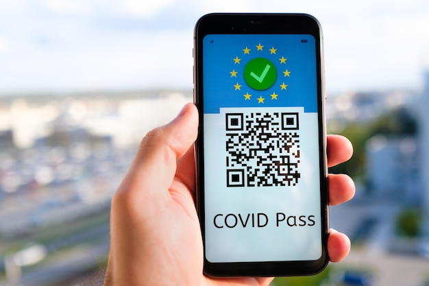 Covid passa com código qr na tela do smartphone na mão do homem no fundo da paisagem urbana