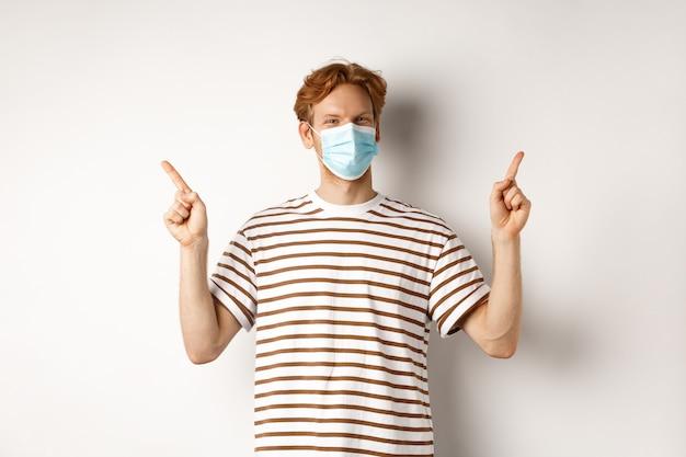 Covid, vírus e conceito de distanciamento social. jovem bonito, com cabelo ruivo, usa máscara facial e aponta de lado para duas ofertas promocionais, com fundo branco.