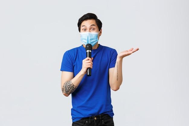 Covid019 estilo de vida, emoções de pessoas e lazer no conceito de quarentena. entusiasmado homem asiático em máscara médica tem discurso, usando microfone, ator de stand-up comédia contando piadas para o público