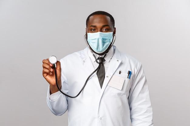 Covid19, check-up hospitalar e conceito de saúde. médico afro-americano bonito, médico chegou ao paciente com estetoscópio, tratando os sintomas do coronavírus com pulmões, capacidade respiratória