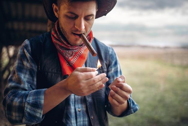Cowboy barbudo acende um charuto, cultura do oeste selvagem