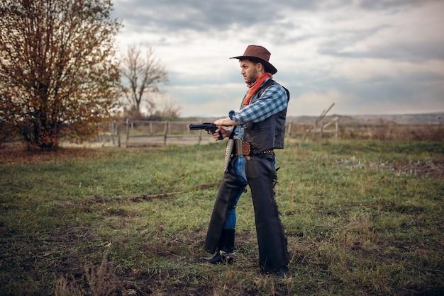 Cowboy brutal com revólver, tiroteio no rancho do texas, oeste. homem vintage com arma, estilo de vida do faroeste