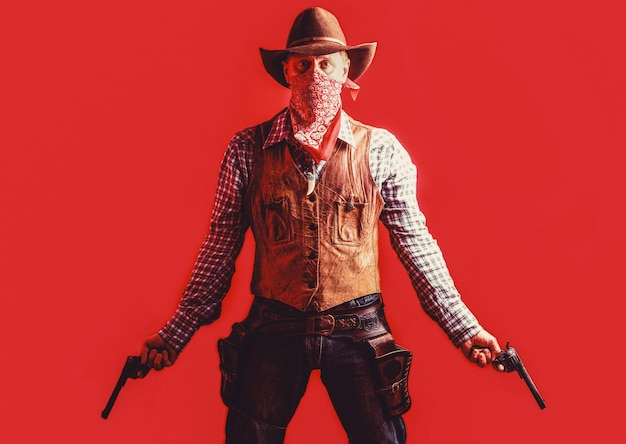 Cowboy com arma em fundo vermelho. bandido americano na máscara, homem ocidental com chapéu. fazendeiro ou cowboy de chapéu. homem com chapéu de cowboy, arma. oeste, armas.