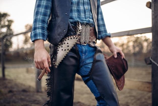 Cowboy com roupas de couro posa com cigarro