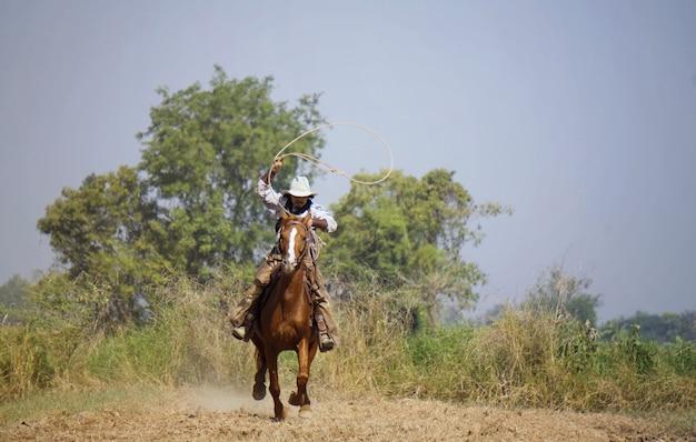 Cowboy com um cavalo e uma arma na mão