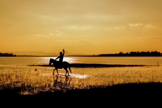 Cowboy de silhueta a cavalo