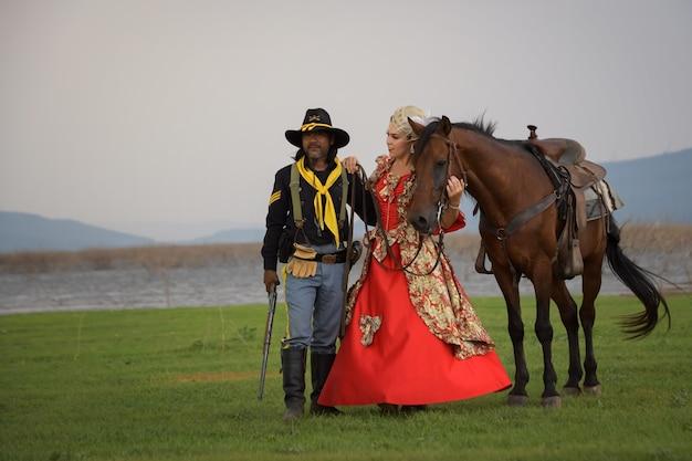 Cowboy e uma linda mulher usando um vestido longo estilo ocidental