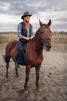Cowboy em roupas de couro montando um cavalo na fazenda