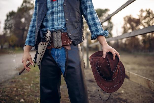 Cowboy em roupas de couro posa com cigarro no curral de cavalos