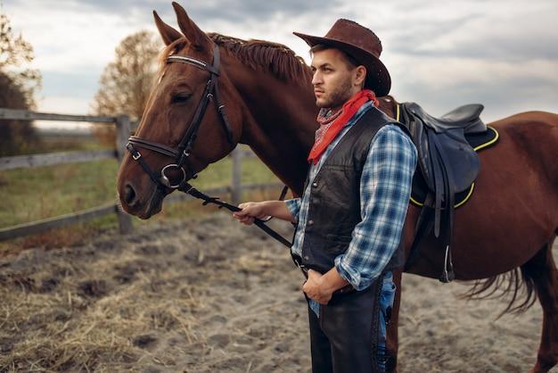 Cowboy posa com cavalo na fazenda do texas