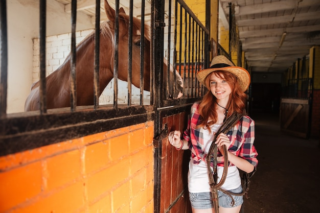 Cowgirl alegre e bonita jovem com seu cavalo no rancho