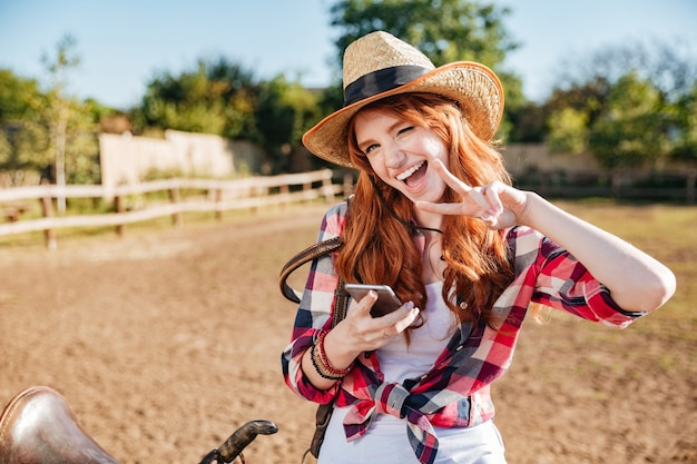 Cowgirl alegre e brincalhão de chapéu usando o celular e mostrando o símbolo da paz