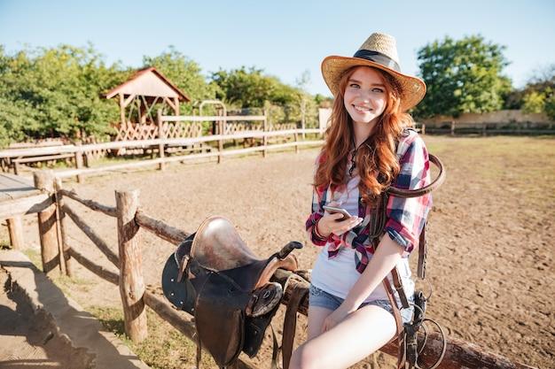 Cowgirl bonita sorridente em pé e usando o celular no rancho