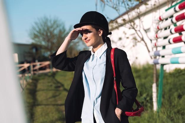 Cowgirl jovem concentrada em pé ao ar livre