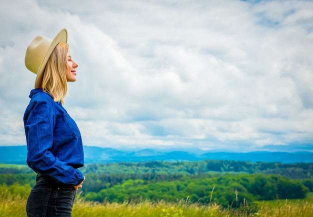 Cowgirl loira com chapéu no prado com montanhas atrás
