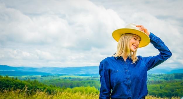 Cowgirl loira com chapéu perto de um carro em um prado com montanhas atrás
