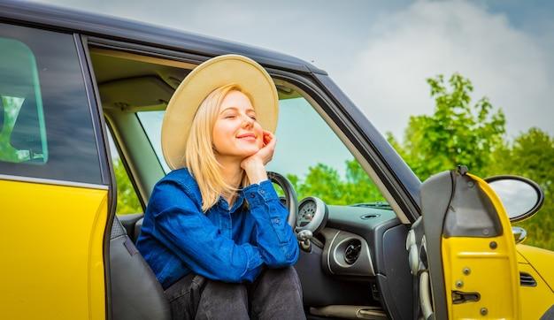 Cowgirl loira com chapéu sentado em um carro no campo