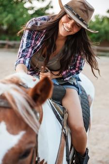 Cowgirl muito jovem e alegre desfrutando de um passeio a cavalo na aldeia