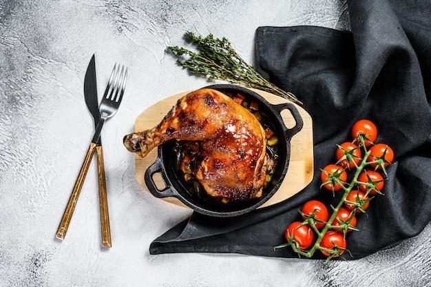 Coxa de frango assada com temperos em uma frigideira. fundo cinza. vista do topo