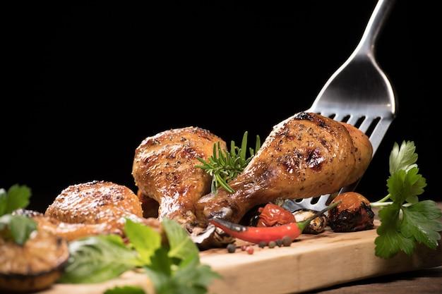 Coxa de frango assado e vários legumes em uma tábua