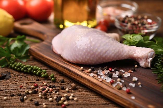 Coxa de frango cru fresco com ingredientes para cozinhar em uma tábua de madeira