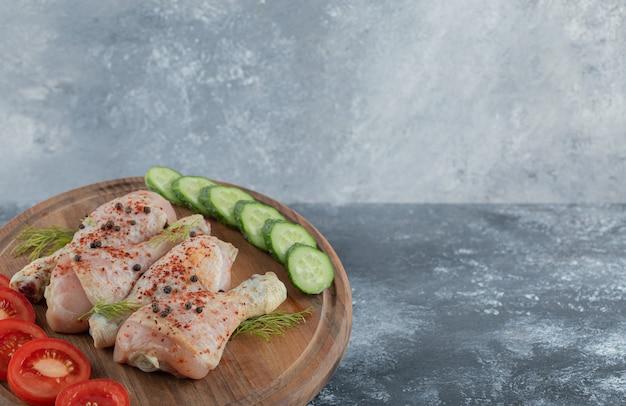 Coxa de frango cru marinado com vegetais na placa de madeira.