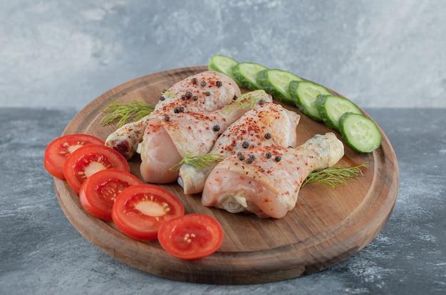 Coxa de frango cru marinado na placa de madeira com vegetais fatiados.