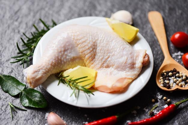 Coxa de frango cru no prato branco para cozinhar alimentos limão frango alecrim na mesa de alimentos