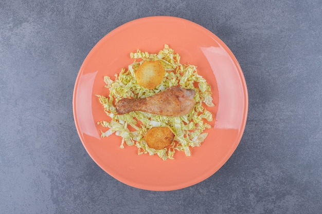 Coxa de frango e batatas fritas no prato laranja.