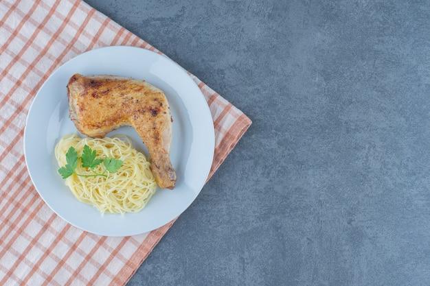 Coxa de frango e espaguete no prato branco.