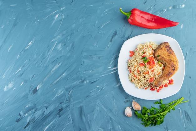 Coxa de frango e macarrão em um prato ao lado de legumes, no fundo de mármore.