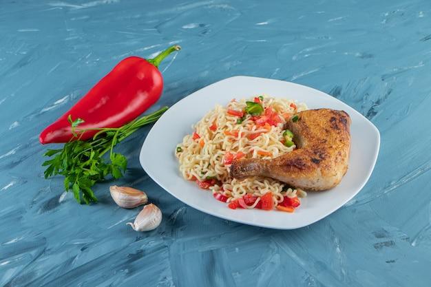 Coxa de frango e macarrão em um prato ao lado de vegetais, na superfície de mármore.