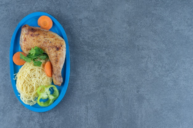 Coxa de frango frito e espaguete na placa azul.