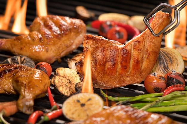 Coxa de frango grelhado com vários legumes na grelha flamejante