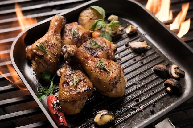 Coxa de frango grelhado com vários legumes na panela na grelha flamejante