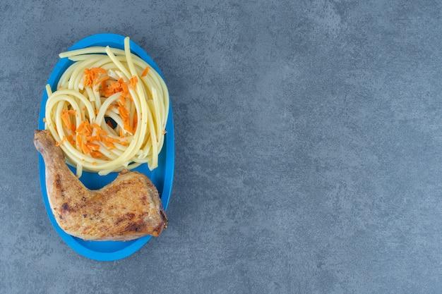 Coxa de frango grelhado e espaguete na placa azul.