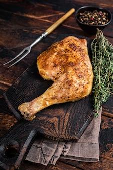 Coxa de frango grelhado em uma placa de madeira. fundo de madeira escuro. vista do topo.