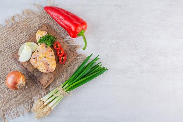 Coxa de frango marinada com vegetais orgânicos na superfície de pedra