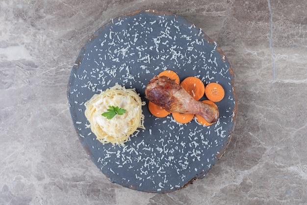 Coxa de frango na cenoura fatiada ao lado de espaguete na placa de madeira, no mármore.