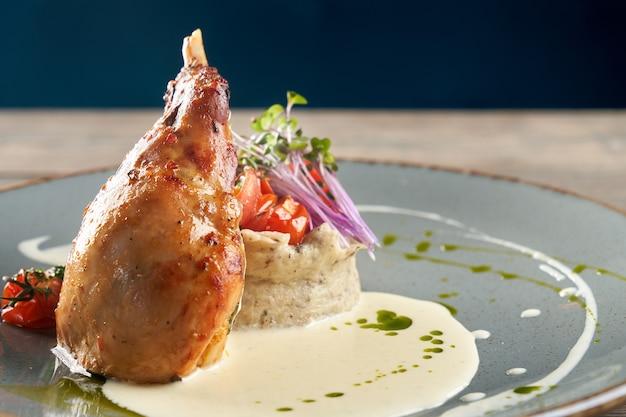 Coxa de frango servida com purê de batata e legumes