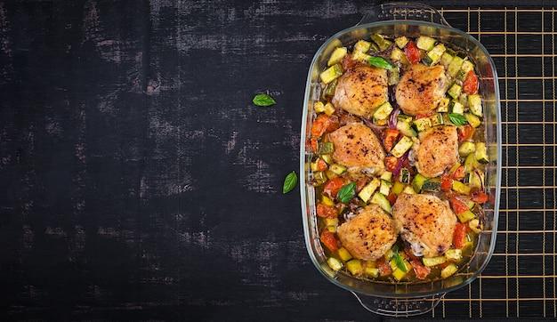 Coxas de frango assado, abobrinha e legumes em uma assadeira sobre uma mesa escura. vista superior, sobrecarga