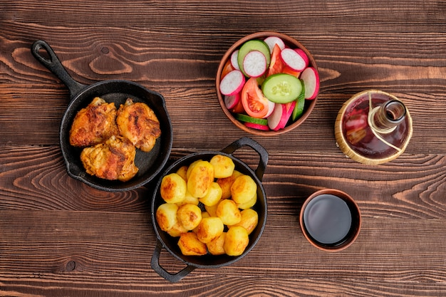 Coxas de frango assado, batata frita e salada - jantar rústico