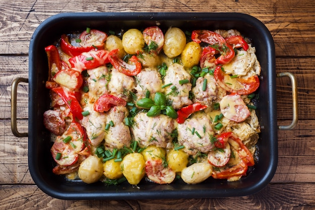 Coxas de frango assado, batatas e legumes em uma assadeira em uma mesa de madeira,